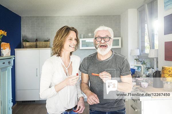 Lachendes reifes Paar in der Küche zu Hause
