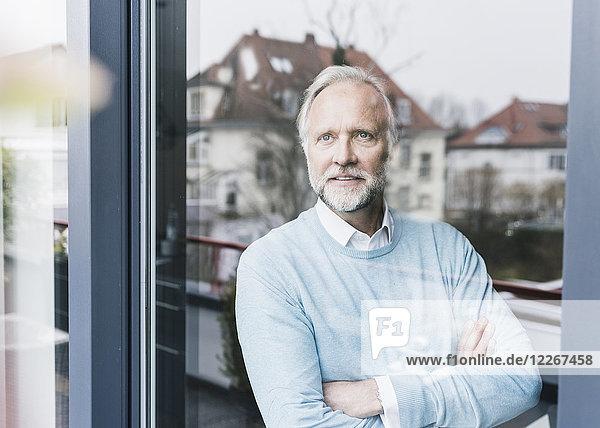Porträt eines reifen Mannes mit Blick aus der Glastür