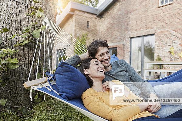 Glückliches Paar in der Hängematte im Garten des Hauses liegend