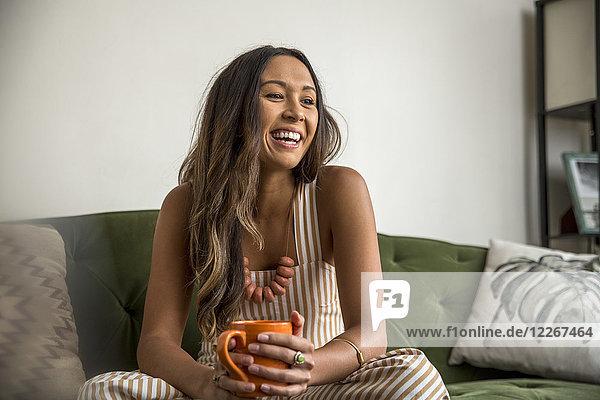 Lachende junge Frau mit Kaffeetasse auf der Couch sitzend
