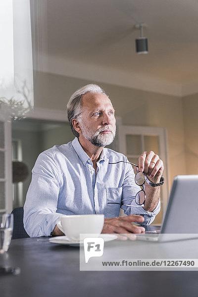 Porträt eines nachdenklichen reifen Mannes  der am Tisch sitzt und mit dem Laptop in die Ferne schaut.