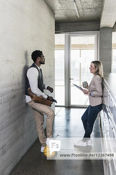 Gelegenheitskaufmann und Geschäftsfrau diskutieren im Bürogeschoss