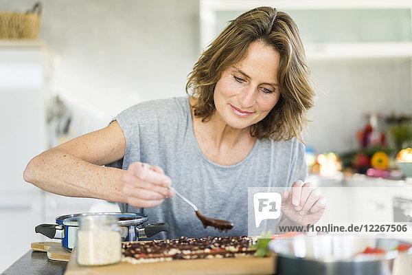 Frau macht Erdbeerschokolade in der Küche zu Hause