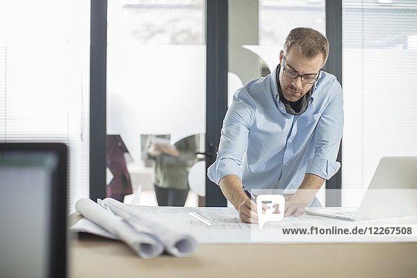 Man making notes on plan in office
