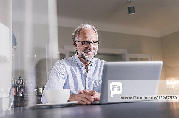 Porträt eines lächelnden  reifen Mannes  der zu Hause am Tisch sitzt und einen Laptop benutzt.