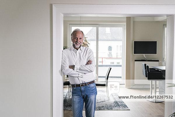 Porträt eines lächelnden  reifen Mannes  der sich in seiner Wohnung an den Türrahmen lehnt.