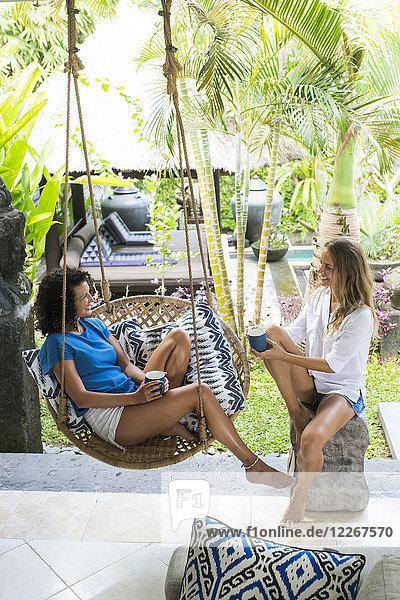 Zwei lächelnde Frauen  die auf der Terrasse bei einer Tasse Kaffee reden.