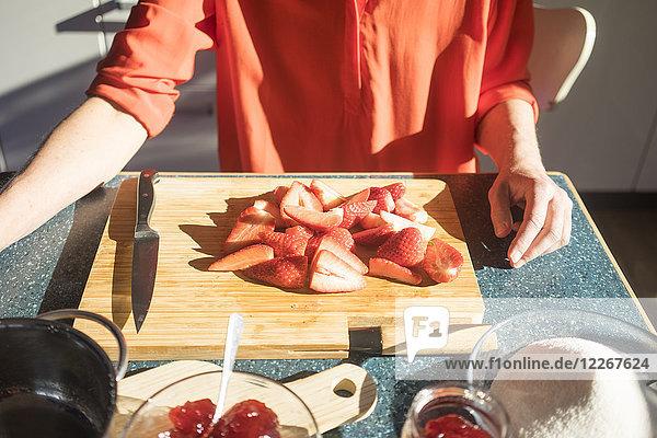 Nahaufnahme einer Frau  die Erdbeermarmelade in der heimischen Küche herstellt.