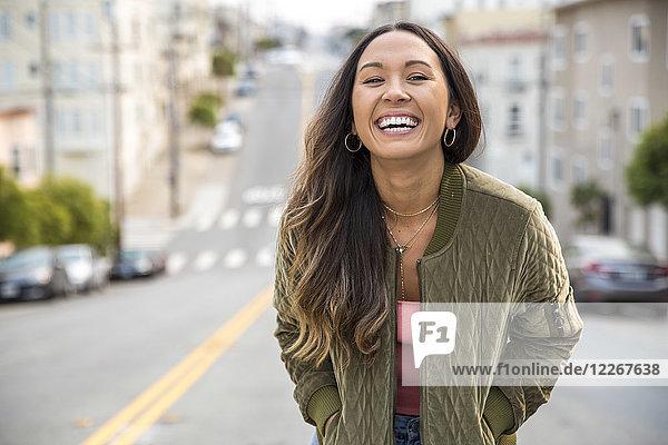 Porträt der lachenden jungen Frau auf der Straße
