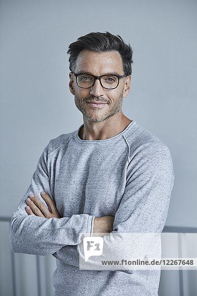 Porträt eines lächelnden Mannes mit Stoppel in grauem Sweatshirt und Brille