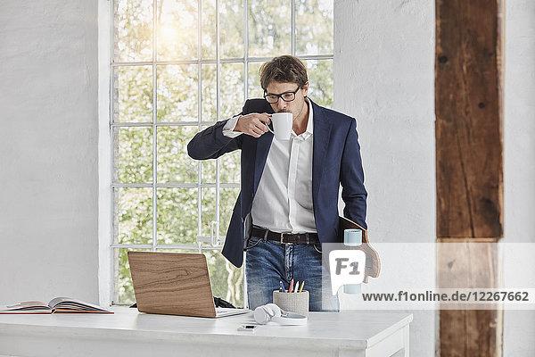 Geschäftsmann mit Skateboard  der Kaffee trinkt und den Laptop auf dem Schreibtisch anschaut.