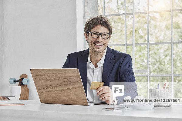 Porträt des lächelnden Geschäftsmannes mit Laptop auf dem Schreibtisch mit Kreditkarte