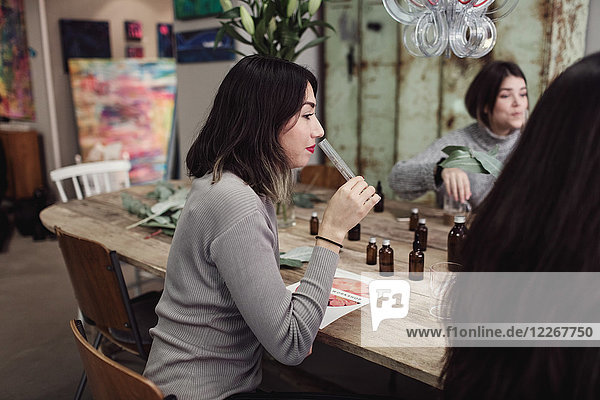 Side view of young woman smelling liquid from test tube while sitting with colleagues at table in workshop