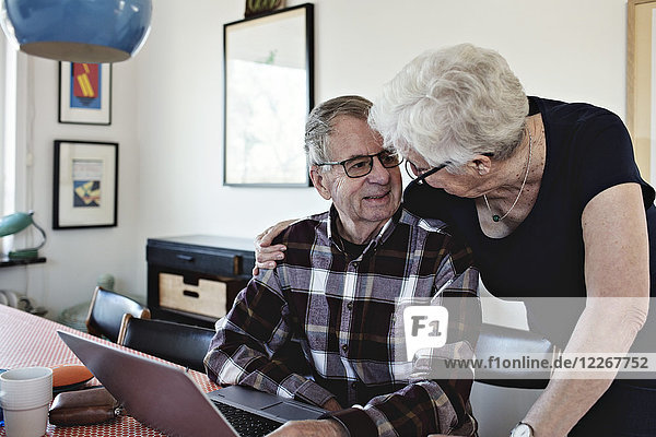 Smiling senior couple with laptop at dining table