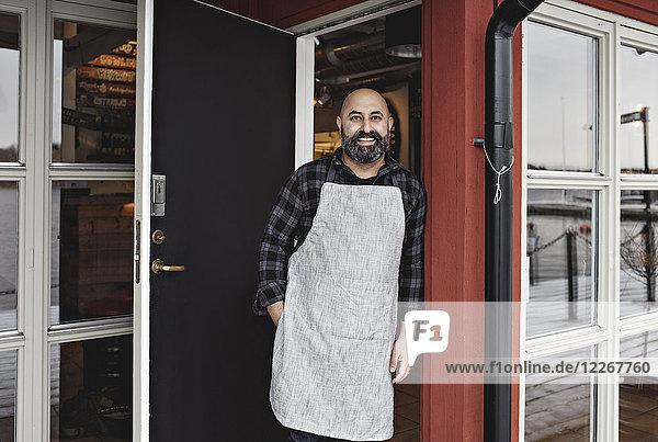 Portrait of smiling worker standing at doorway by restaurant