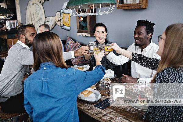 Fröhliche Freunde stoßen beim Sitzen am Esstisch im Restaurant an.