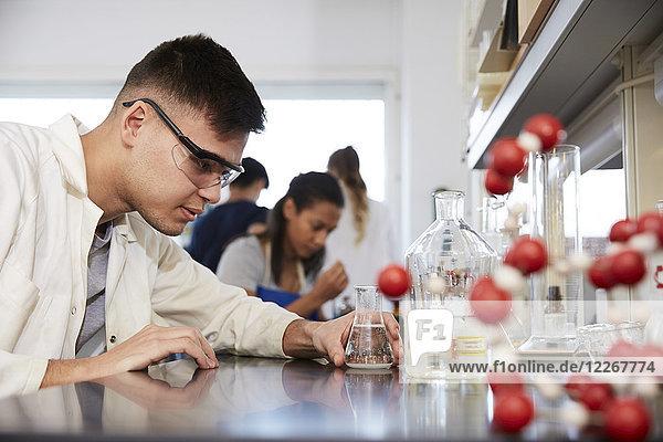 Zuversichtlicher junger  männlicher Chemiestudent von Freunden im Labor der Universität