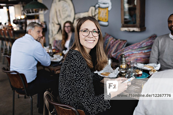 Portrait of smiling woman holding mobile phone while sitting with friends at table