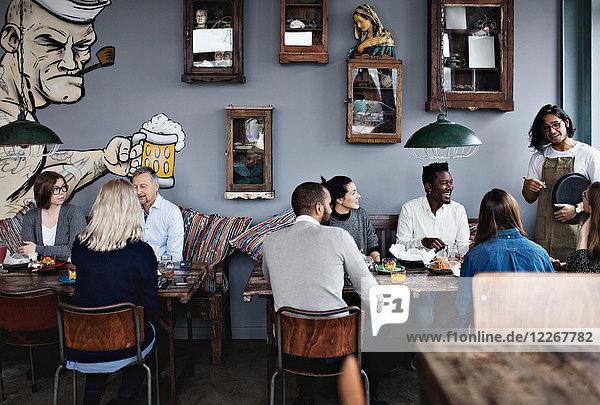 Besitzer im Gespräch mit multiethnischen Freunden beim Brunch mit der Familie im Restaurant