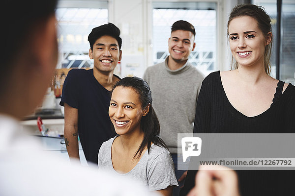 Happy multi-ethnic students looking at female teacher in chemistry laboratory