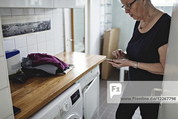 Seniorin im Bad stehend mit dem Handy zu Hause