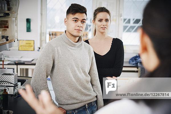 Junge Chemiestudenten suchen Lehrerin im Labor