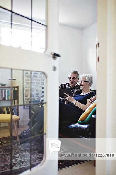 Full length of smiling senior couple sitting on sofa with digital tablet seen from ajar door