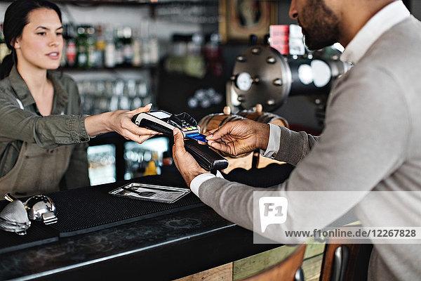 Mittelteil des Kunden  der die Kreditkartenzahlung an der Kasse durchführt.