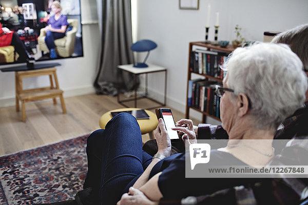 Hochwinkelansicht eines älteren Paares  das zu Hause mit einem Smartphone fernsieht.