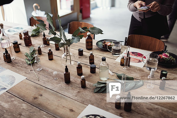 High angle view of various perfume bottles on table by woman photographing at workshop