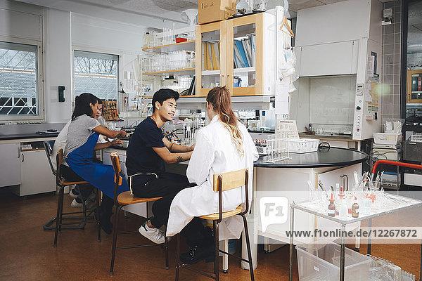 Multi-ethnische junge Universitätsstudenten sitzen auf Lehrstühlen im Chemielabor