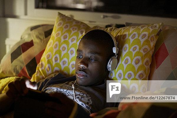 Nahaufnahme eines Jungen mit Kopfhörer über ein digitales Tablett  während er zu Hause auf dem Bett liegt.