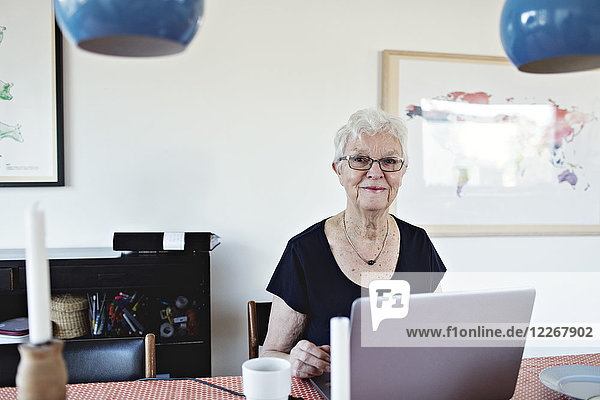 Portrait of smiling retired senior woman sitting with laptop at dining table