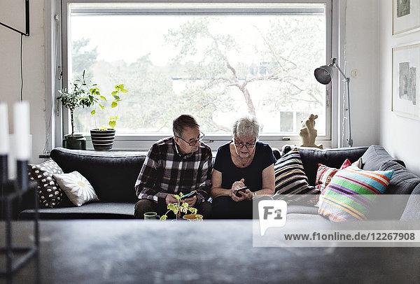 Senioren-Paar mit Smartphones auf dem Sofa im Wohnzimmer gegen das Fenster zu Hause sitzen