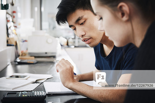 Young university students studying together in classroom