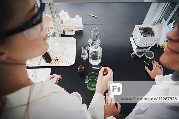 Hochwinkelansicht junger multiethnischer Studenten,  die mit flüssigen Lösungen im Chemielabor stehen.