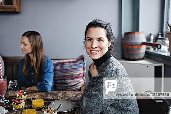 Porträt einer lächelnden Frau beim Brunch mit Freundin am Tisch