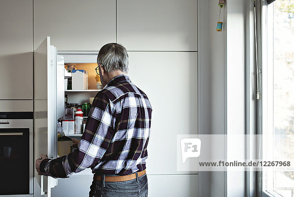 Rear view of retired senior man standing by open fridge door in kitchen at home