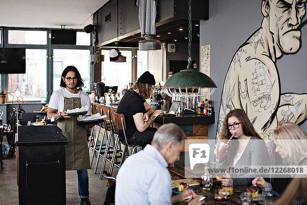 Junger Kellner serviert Speisenteller beim Spaziergang inmitten der Kunden im Restaurant