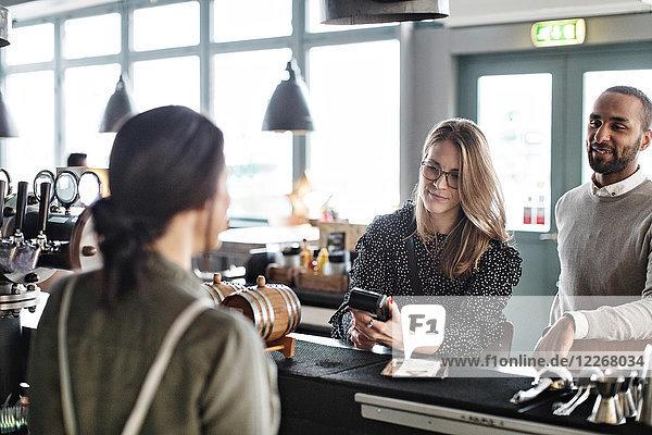 Frau  die Kreditkartenzahlung an die Besitzerin leistet  während sie an der Kasse steht.