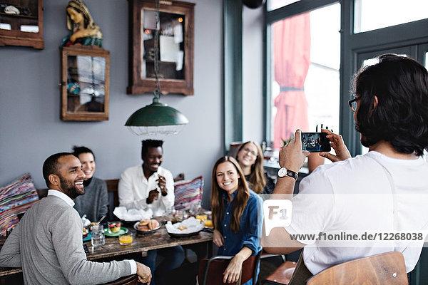 Besitzer fotografiert lächelnde Freunde per Handy am Tisch im Restaurant