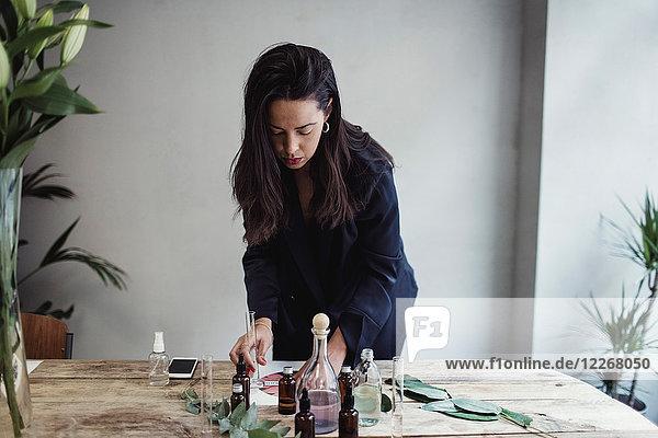 Mid adult female entrepreneur preparing perfume on table against wall at workshop