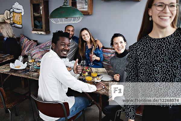 Fröhliche multiethnische Freunde beim Brunch im Restaurant