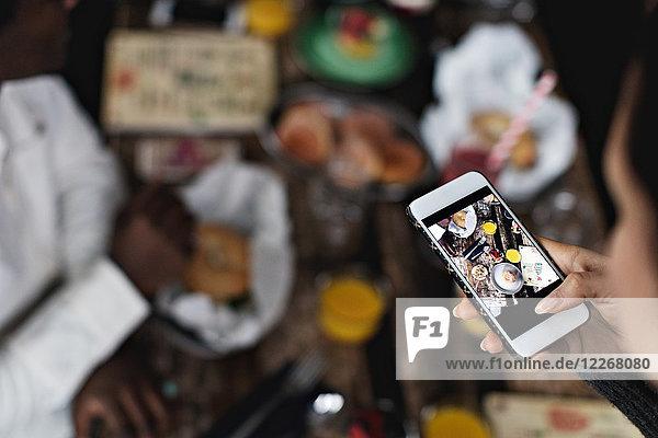 Abgeschnittenes Bild einer Frau  die Essen auf dem Esstisch im Restaurant fotografiert.