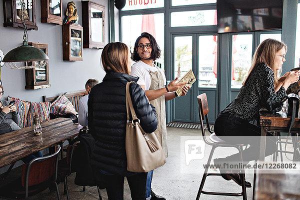 Besitzerin im Gespräch mit Kundin im Restaurant