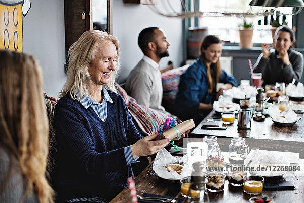 Lächelnde reife Frau  die ein Geschenk hält  während sie mit ihrer Tochter am Esstisch im Restaurant sitzt.