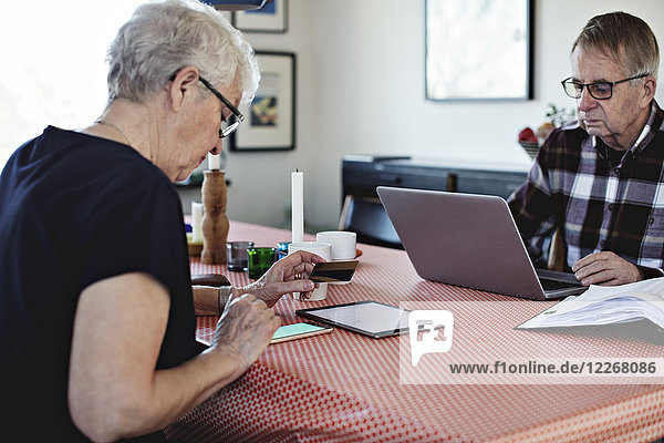Senior couple using technologies while sitting at dining table