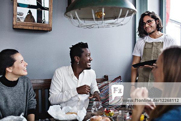 Fröhliche Freunde  die den jungen Kellner beim Brunch im Restaurant anschauen