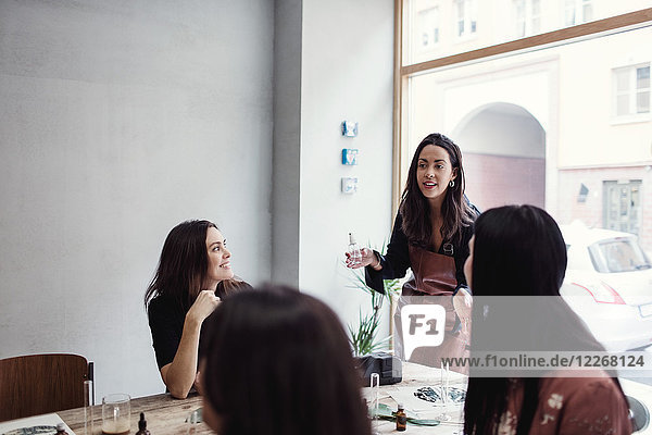 Confident female owner standing with perfume explaining to colleagues at workshop