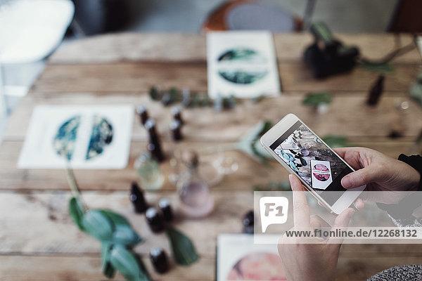 Abgeschnittene Hände der mittleren erwachsenen Besitzerin beim Fotografieren von Broschüren und Parfümflaschen auf dem Tisch in der Werkstatt.